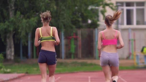 Dva sportovci soutěží v běhu. Pohled zezadu.