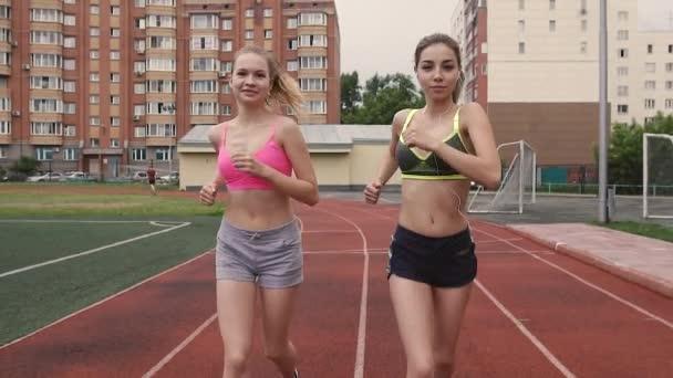 Portrét dvou mladých sportovců, kteří soutěží v závodu na stadionu v ráno, léto, venku