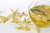 Photo of herbal tea in a transparent cup. flowers and leaves of herbs. flowers of linden and elderberry, leaves of mint. time for relaxation. hot tea. use for background, text, for your design, card