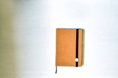 Notebook (beige, brown), lying on a white table, illuminated by natural muted daylight.