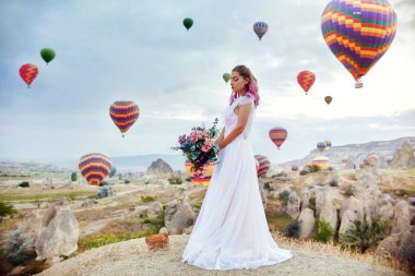 Woman in a long dress on background of balloons in Cappadocia. Girl with flowers hands stands on a hill and looks at a large number of flying balloons. Turkey Cappadocia fairytale scenery of mountains