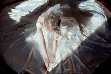 Beautiful slender blonde girl sitting on the floor in long white