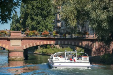 Tourist entertainment in Strasbourg, France with a boat trip on river Ill, under a vintage bridge and trees, on a sunny day of summer.