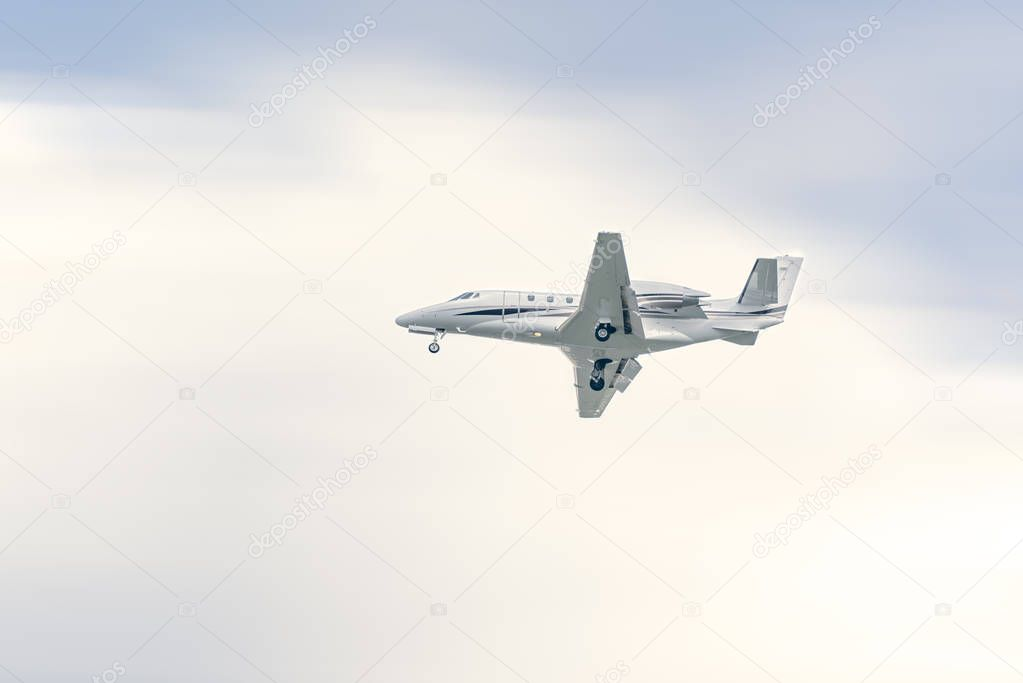Private jet flying at high speed under a blueish sky on a sunny day