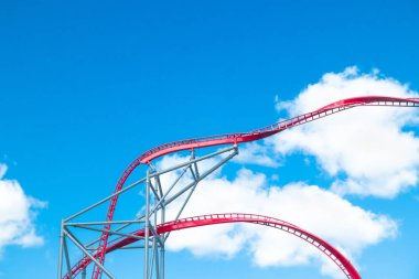 Roller Coaster in amusement park on blue sky background