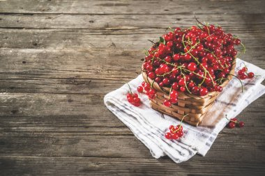 Red currant in small basket, rustic wooden table copy space