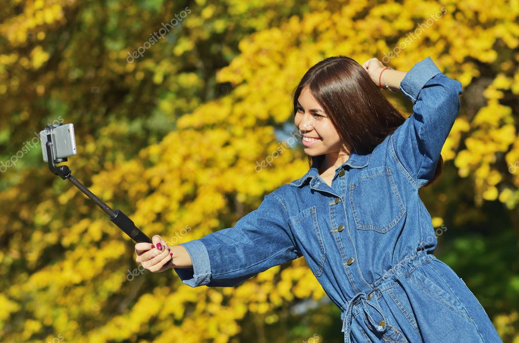 A young beautiful girl in a denim suit takes a selfie walking in the city Park in the autumn, horizontal photo
