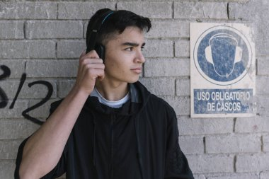 Teenager with headphones next to a mandatory headphone signal