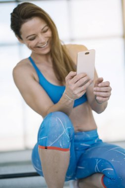 Woman with phone in gym