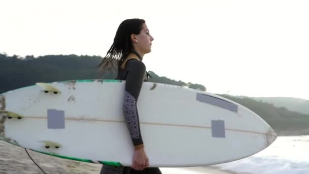 Young woman surfing the wave on his surfboard