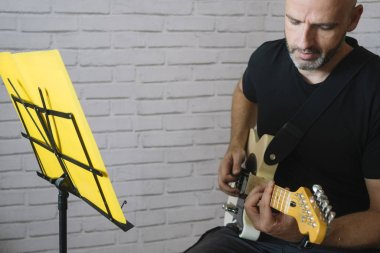 Man studying music with electric guitar at home