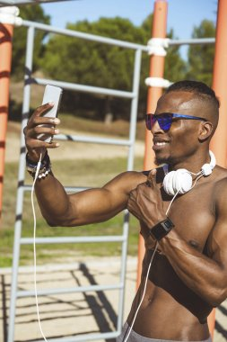 Athlete man training outdoors with mobile.