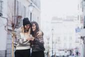Két nő az utcán smartphone