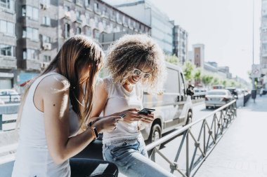 Beautiful women using a mobile in the Street.