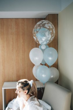 Woman who gave birth in a hospital room with blue balloons