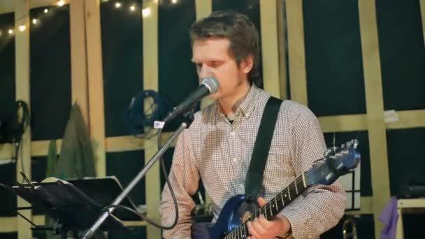 Muž kytarista hraje na kytaru a zpívat píseň