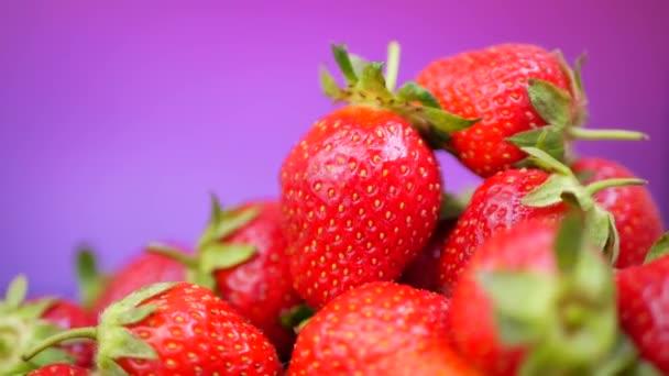 Čerstvé jahody v misce na purpurové nebo fialové pozadí
