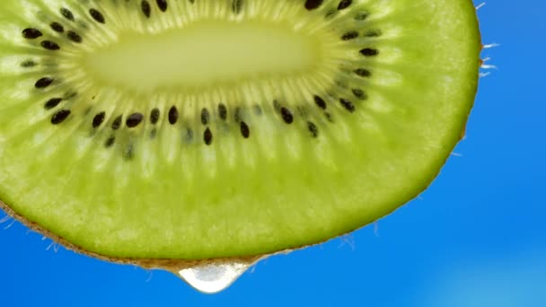 Drop of pure water or juice dripping from slice of kiwi