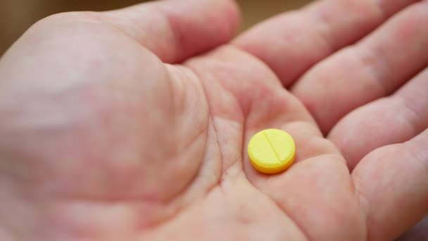 Person pouring bunch of prescription yellow opiate pills into hand
