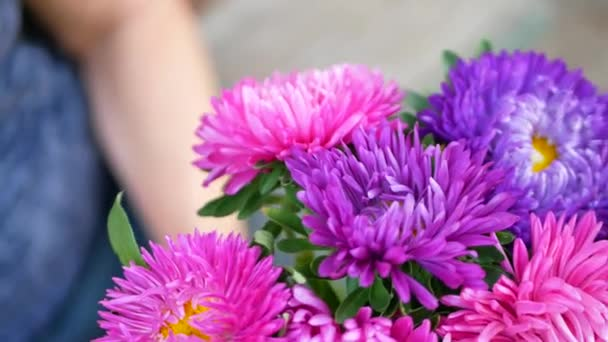 Woman florists hands making bouquet with michaelmas daisy or aster