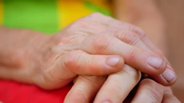 Vecchie mani di donna senior con pelle rugosa