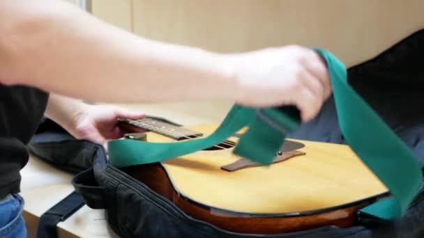Gitarrist faltet Akustikgitarre nach Konzert in schwarzen Koffer