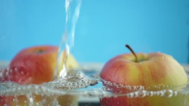 Červené žluté jablko pod vodou se stezka průhledné bubliny