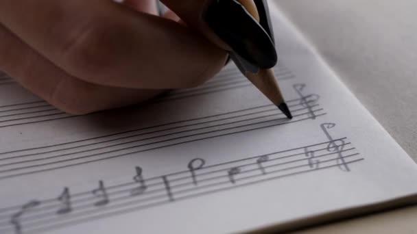 Zenész vagy zeneszerző kézzel ír egy dalt vagy zenei alkotás
