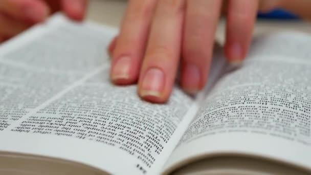 Zenske rukou otevřít knihu na stůl a najít požadované informace