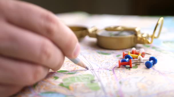 Mens finger planning trip with compass and multicolored pins. Trip route destination on map concept