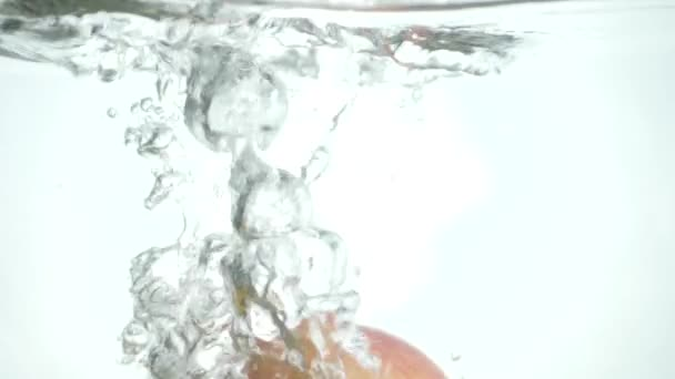 Red yellow apple under water with a trail of transparent bubbles