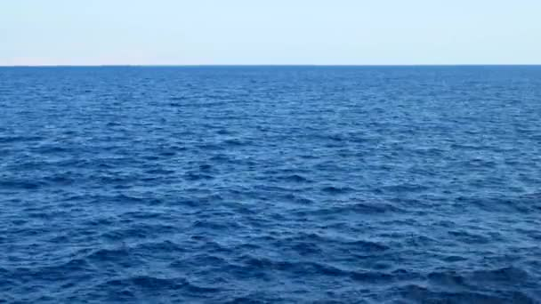 Modrá mořská voda s bílou pěnou na pozadí