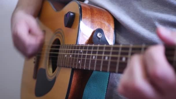 Muž si hraje akustické dřevěné 6 strunná kytara