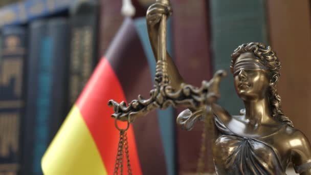Statue of Lady Justice with Bookshelf with Books and Germany Flag Background