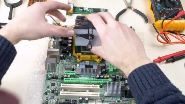 junger Mann installiert CPU-Kühler Lüfter auf der Hauptplatine