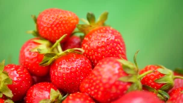 Čerstvé jahody v míse na zeleném pozadí