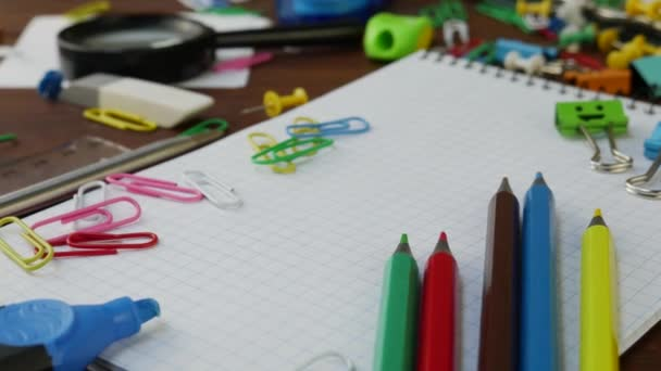 Multicolored Pencils, Paper Clips and Notebook on Brown Wooden Desk