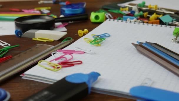 Tarka ceruza, gemkapcsok és jegyzetfüzet-ra barna fa iskolapad