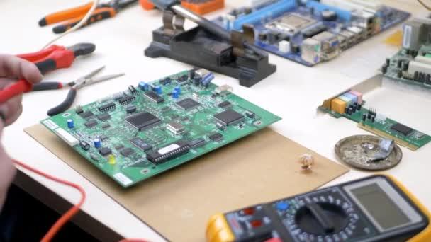 Service-ccenter-Mitarbeiter mit Tester-Checks auf Wartbarkeit grünes Motherboard