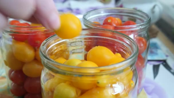 Female Hand Puts on Yellow Tomatoes in Jar on Kitchen Table