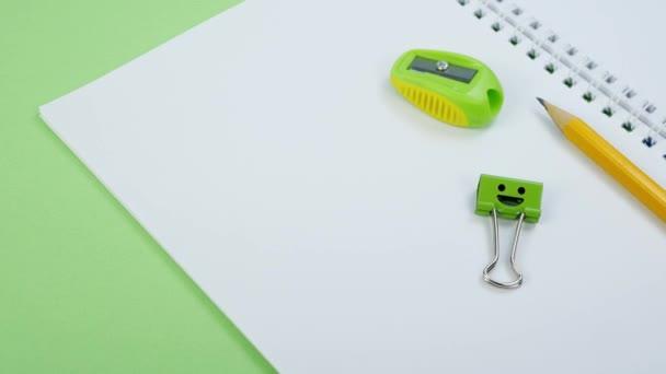 Sárga ceruza és zöld mosoly Binder Clip az iskola jegyzettömbjén