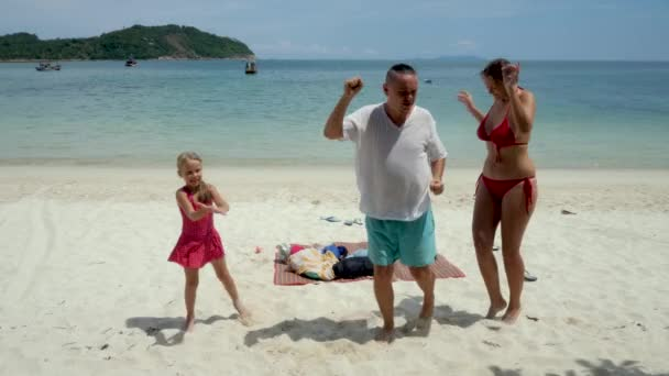 Cute mother, father and daughter enjoy dance, jump and smile on sea beach