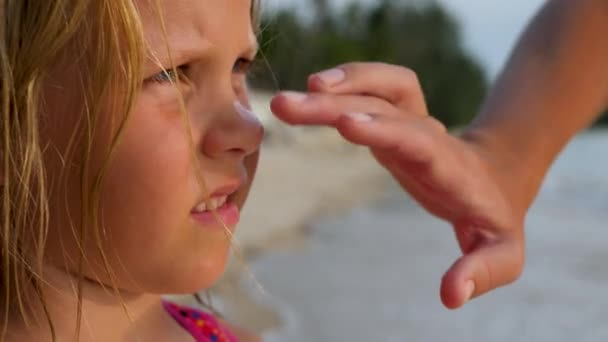 Mother apply sunscreen cream on daughters nose