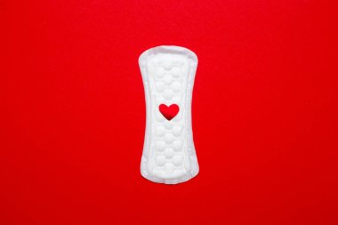 menstruation concept. an image of a menstrual pad on red background