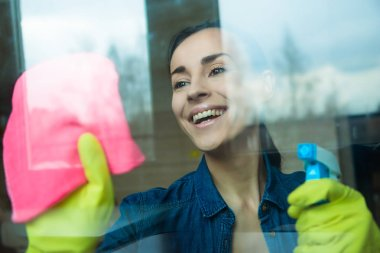 Beautiful young woman using a duster and a spray while cleaning windows in the house