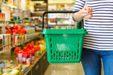 woman holding shopping basket and buying products in supermarket