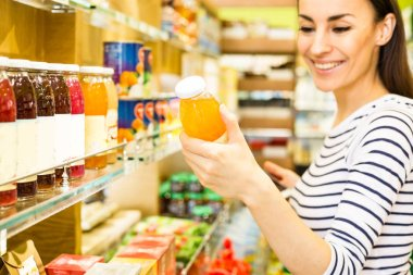 Smiling young caucasian woman choosing products from shelves in supermarket