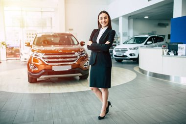 Beautiful smiling saleswoman in suit standing with crossed arms on dealership cars background, full length