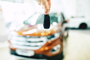 Male hand holding car keys. View of row new car at dealership indoors