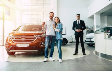 Happy young family standing with car key in dealership, male manager and car on background, full length